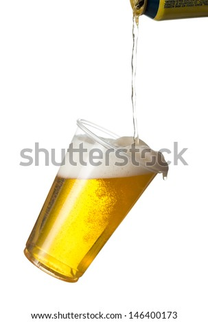 Golden beer, ale or lager in a tilting plastic disposable cup or glass with beer being poured from can and spilling over edge of pint - stock photo