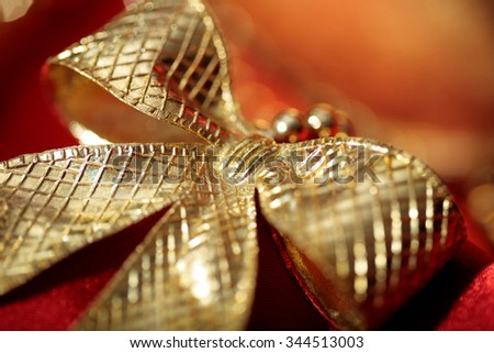golden  bow close-up on red holiday background  - stock photo