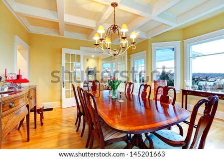 Golden bright yellow luxury dining room with elegant classic furniture and white wood ceiling. - stock photo