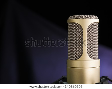 golden broadcast voice microphone on dark background - closeup shot - stock photo