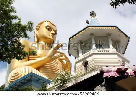 Golden Buddha and temple in Dambulla, Sri Lanka - stock photo