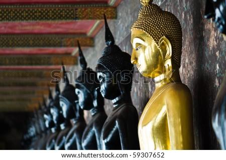 Golden Buddha between black Buddhas, Wat Pho, Thailand - stock photo