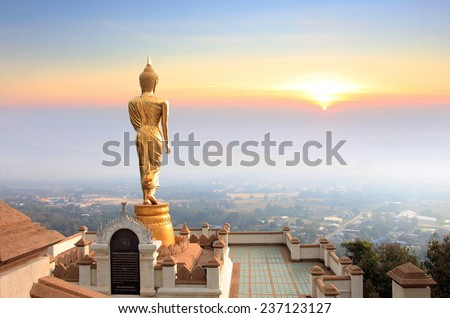 Golden Buddha statue standing on a mountain Wat Phra That Khao Noi, Nan Province, Thailand, City of cultural and natural tourism in the north where the air is cool.  - stock photo