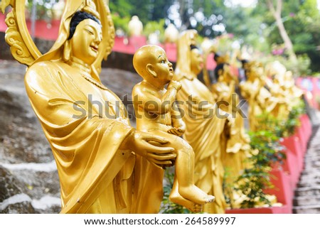 Golden Buddha statues along the stairs leading to the Ten Thousand Buddhas Monastery in Hong Kong. Hong Kong is popular tourist destination of Asia. - stock photo