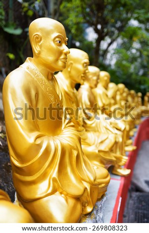 Golden Buddha statues along the stairs leading to the Ten Thousand Buddhas Monastery on nature background in Hong Kong. Hong Kong is popular tourist destination of Asia. - stock photo
