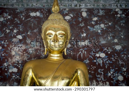 Golden buddha with sash close up against a decorative floral patterned background in a Buddhist temple in Bangkok Thailand - stock photo