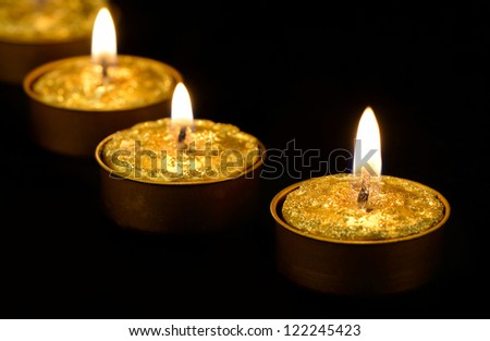 Golden burning candles on a black background. - stock photo