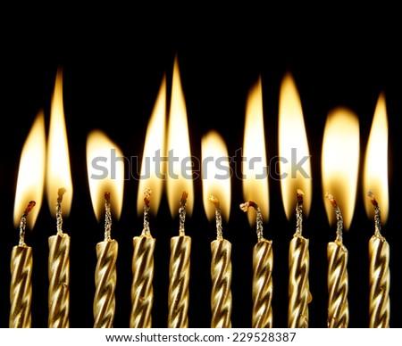 Golden burning candles on black background  - stock photo