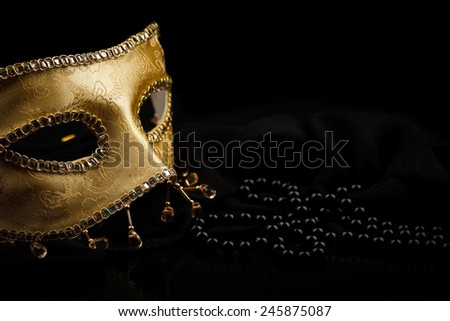 Golden carnival mask and pearls on black background - stock photo