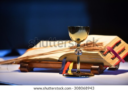 Golden chalice and Roman Misal book in the background. - stock photo