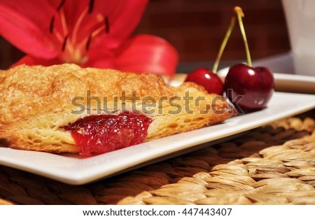 Golden cherry turnover and two, red cherries on a white plate, white tea cup and red (cherry color) lily on natural weaved place mat.  - stock photo