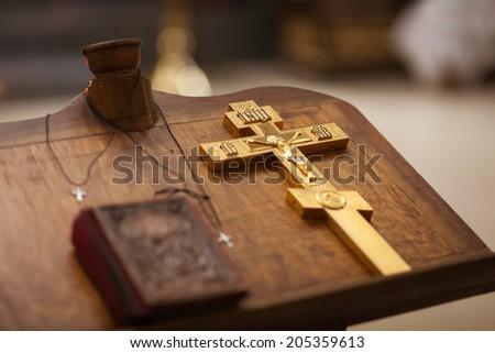 Golden christian cross on table in church - stock photo