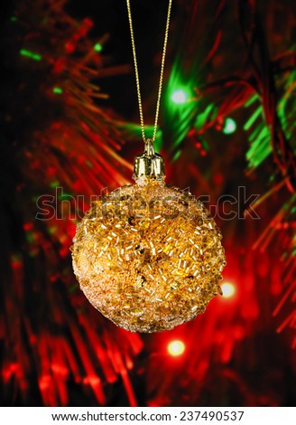 Golden christmas ball on the defocused background of blurred Christmas lights at night - stock photo