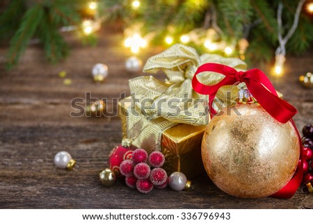 golden  christmas balls and gift box on wooden table with defocused christmas lights in background - stock photo
