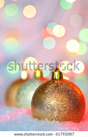 Golden Christmas baubles on snow against glaring background - stock photo