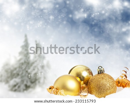 Golden Christmas decorations and gift box in the snow, snow cowered pine trees in the background - stock photo