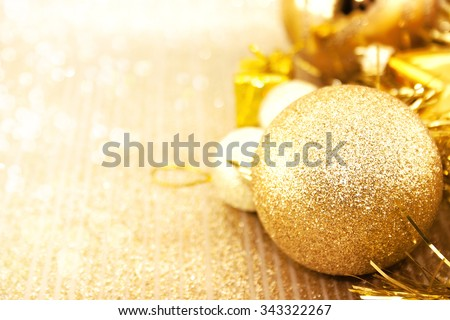 Golden Christmas decorations on shiny background with copy space for text. Christmas background or greeting card. Selective focus. - stock photo