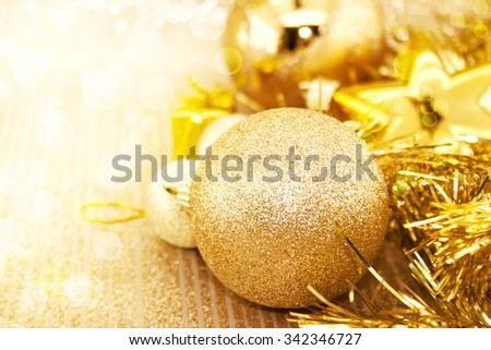 Golden Christmas decorations on shiny background with copy space for text. Holiday background or greeting card. Selective focus.  - stock photo