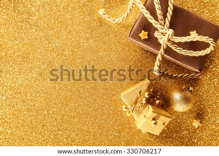Golden Christmas gift border with decorative luxury gifts over a textured gold background with copyspace for your seasonal greeting - stock photo