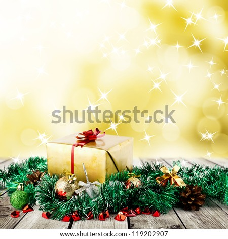 Golden christmas gift box with christmas balls on wood planks over abstract blur yellow background - stock photo
