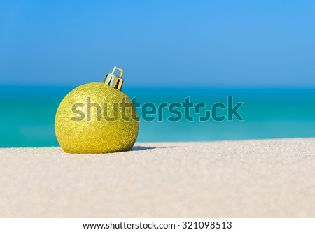 Golden christmas tree ball on ocean beach sand - winter holidays in hot countries concept - stock photo