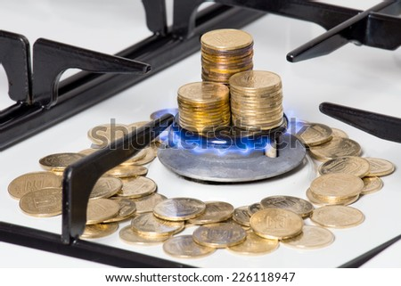 Golden coins around natural gas cooker burner with fire - stock photo
