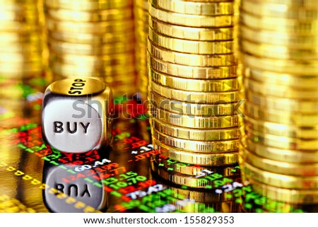 Golden coins, financial chart and dices cube with the word BUY. selective focus - stock photo