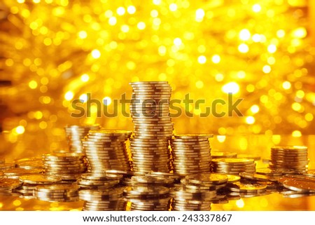 Golden coins stack with golden lights bokeh background - stock photo