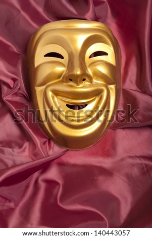 Golden  comedy theatrical mask on satin background - stock photo
