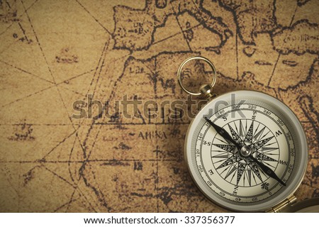 Golden compass on an old map. Selective focus - stock photo