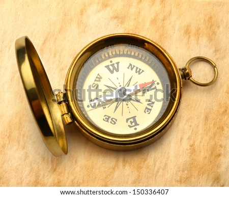 Golden compass on stained paper - stock photo