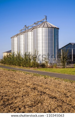 golden corn field in harvest with silo - stock photo