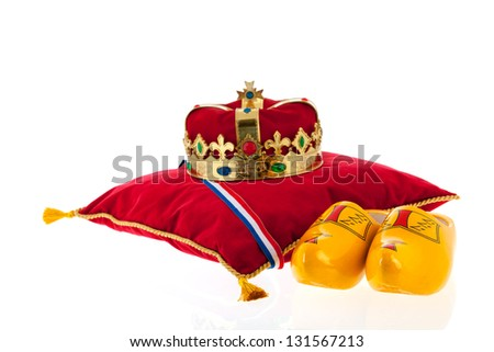 Golden crown on red velvet pillow for coronation in Holland with pair of wooden shoes - stock photo
