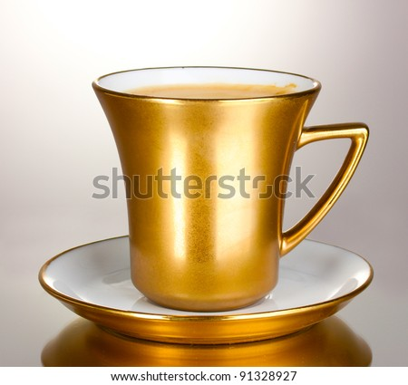 golden cup of coffee isolated on white - stock photo