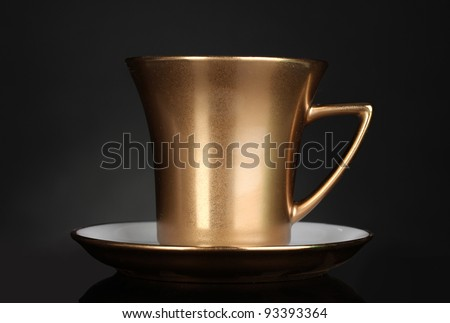 golden cup of coffee on gray background - stock photo