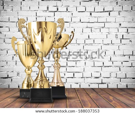 Golden cup trophies on white brick wall - stock photo