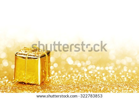 Golden decorative box with holiday gift on gold glitters background - stock photo