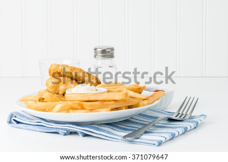Golden deep fried potatoes with battered fish in the background. - stock photo