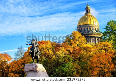 Golden dome of St Isaac Cathedral over the autumnal garden and Peter the Great monument in St Petersburg, Russia - stock photo