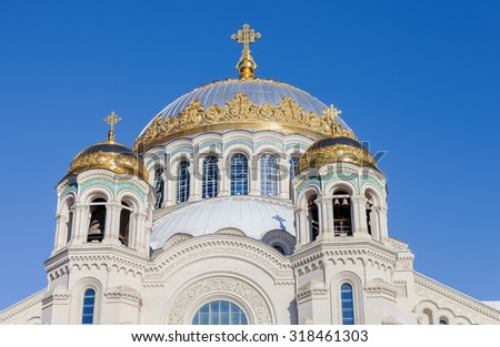 Golden domes with cross of Kronstadt Naval cathedral against blue sky - stock photo