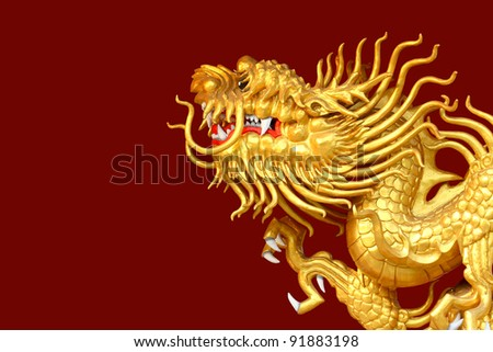 Golden Dragon sculpture with isolated red background - stock photo