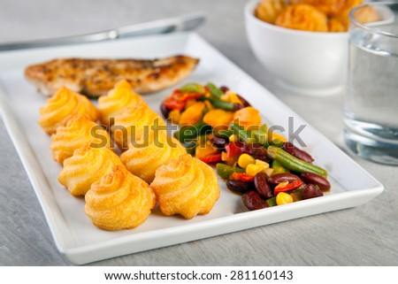 Golden duchess potatoes with grilled chicken and mexican vegetables - stock photo