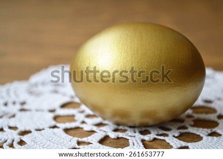Golden Easter egg on the table - stock photo