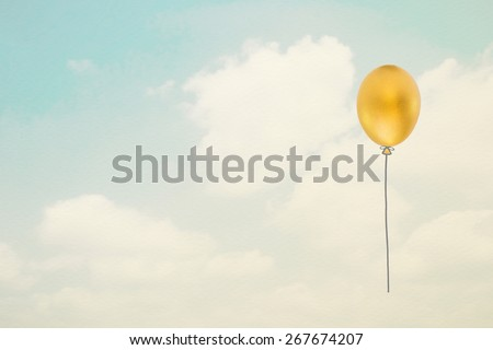 Golden egg in balloon shape floating against the sky in vintage style: A golden egg opportunity concept of fortune and a chance to be rich :  Financial freedom concept of a golden egg opportunity   - stock photo