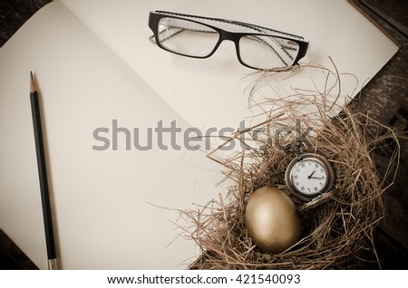 golden egg, pocket watch in the nest, notebook,glasses, pencil over wooden background - stock photo