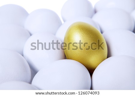Golden egg standing out from other white eggs - stock photo