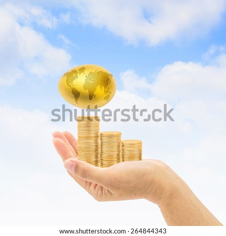Golden egg with world map over golden coin stacks on a hand : A golden egg opportunity concept of fortune a chance to be rich   - stock photo