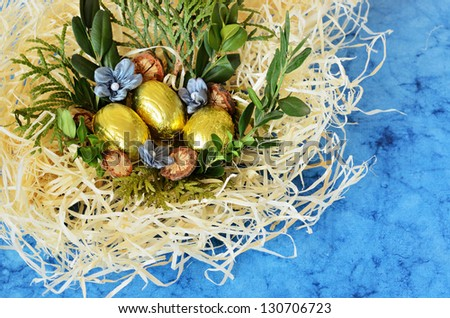 Golden eggs in the nest on a blue background - stock photo