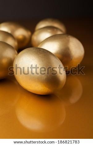 Golden eggs on golden background - stock photo