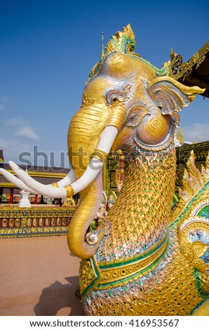 golden elephat statue in front of church - stock photo